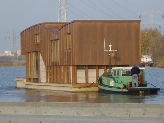 Nieuwbouw woonboot waterwoning in Amsterdam het verslepen naar de ligplaats, het vertrek uit Diemen