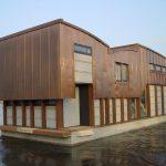 Nieuwbouw woonboot waterwoning in Amsterdam het verslepen naar de ligplaats